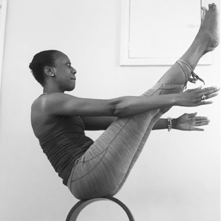 A greyscale image of Donna, in Boat pose whilst balancing on a yoga wheel.