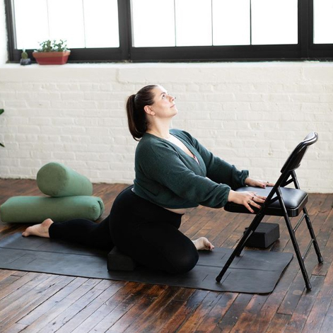 Dana is in a Pigeon pose, supported by yoga blocks and a chair, gaze upwards and with a calm expression.
