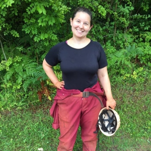 A photo of Sarah in a green woodland area wearing caving overalls and holding a helmet, she is smiling at the camera.