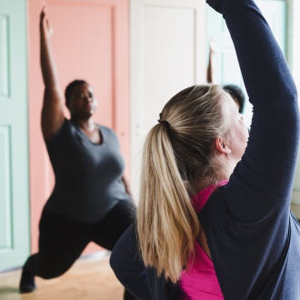 A photograph of two people practicing yoga, both in a Warrior 1 pose. The photograph shows diversity in body type and skin colour.