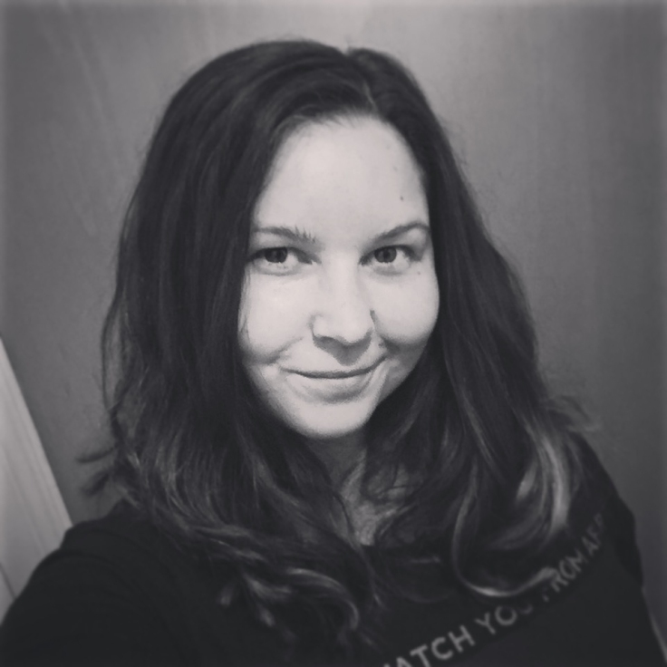 A greyscale 'head and shoulders' photo of Sarah, she is looking at the camera and smiling