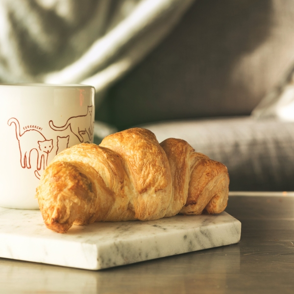 A photo of a hot drink and a croissant with a sofa and blankets in the background.
