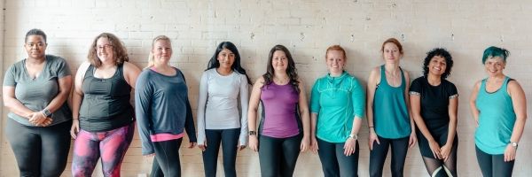 9 people stand against a white brick wall wearing activewear, they look happy, strong and confident.