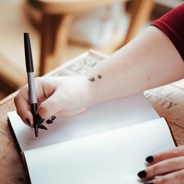 An open notebook on a table and a person sits pen in hand, ready to write.