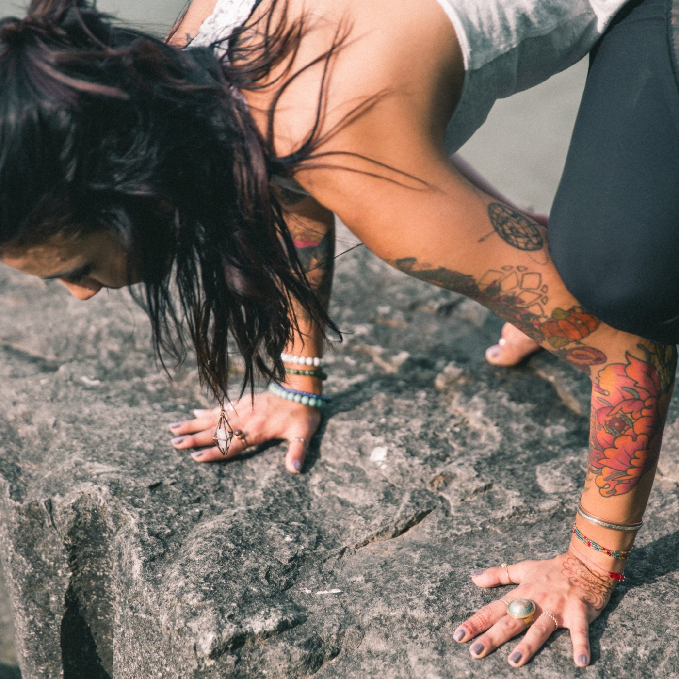 Close up photo of a person practicing crow pose, Bakasana, on a rock near water.