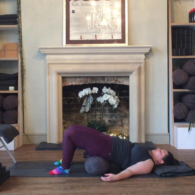 Sarah holds a supported bridge posture. She is lying on her back, her feet on the floor, knees pointing up to the ceiling. A bolster is underneath her lower back, lifting her hips from the floor.