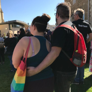 Sarah and her partner Joe stand facing away from the camera, they are attending a climate change protest. Sarah is carrying a rainbow bag and Joe has his arm around Sarah