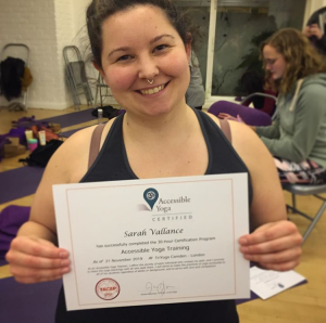 Sarah is holding a certificate and smiling at the camera