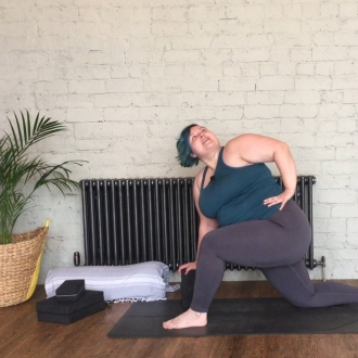 Sarah is in a low lunge posture, right hand resting down on a block while she looks up and over her left shoulder.