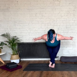 Sarah is in a standing balance pose called Eagle Pose.